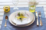 Table setting with blue checkered tablecloth, white napkin