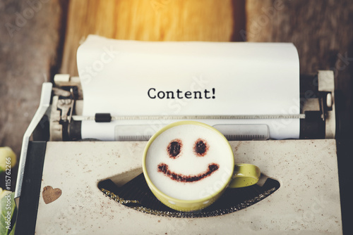 Typewriter with happy face coffee cup, sepia tone. Poster