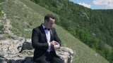 video of groom sitting on the rock on the background of beautifull Mountain View. 4K stock footage clip.