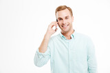 Portrait of smiling confident young businessman talking on mobile phone