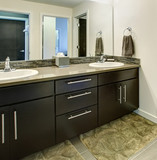 Bathroom interior with black cabinets, two sinks and large mirror.