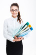 Smiling young business woman in glasses holding folders with documents