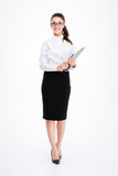 Full length of cheerful business woman standing and holding clipboard