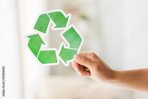 Poster close up of hand holding green recycle symbol