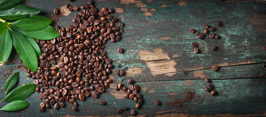 Roasted coffee beans with green leaves on a vintage background, top view with copy space © nerudol