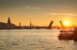 Russia, Saint-Petersburg, 03 July 2016: Closing of Palace Bridge at sunrise, the Peter and Paul Fortress Spike in the orange sky, Rostral colomn, ships, boats, the traffic beginning, sun,