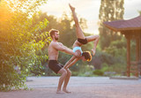Acro yoga, two sporty people practice yoga in pair, couple doing stretching exercise in the garden with evening sunset on background