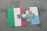 puzzle with the national flag of italy and san marino on a world map background.