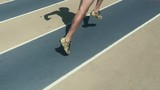 Athlete in gold shoes sprinting in slow motion on faded blue and tan running track