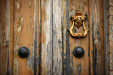 Doorknob on an old wooden door. Tuscany, Italy - 115831039