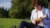 4K Attractive young man playing a ukulele