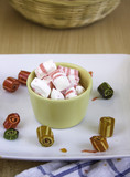 mix of lollipops and candies on the white plate and wooden table, sugar and holiday celebration