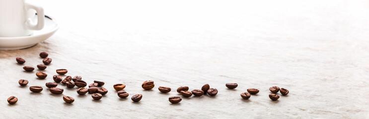 Kaffeebohnen und Kaffeetasse auf heller Steinplatte, Panorama, Makro © v.poth