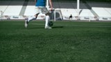 Professional soccer player shooting a ball into the net and goalkeeper preventing goal in slow motion