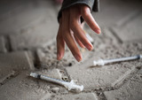close up of addict woman hands and drug syringes