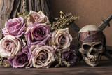 Bouquet purple roses with pirate skull and two swords over tree background on wooden table still life style halloween concept