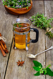Herbal Tea with Thyme, Mint and Cinnamon on Wooden Rustic Backgr