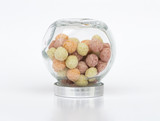 Colorful round cereal puffs in an upside down small glass jar on white background