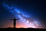 Fototapety Night landscape with Milky Way. Silhouette of a standing young man with raised up arms on the mountain. Beautiful Universe. Travel background with blue night starry sky