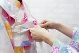 子供に浴衣を着せる母親