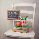 Back to school concept with books, pencils in cup and chalkboard on chair