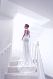 young beautiful bride, back view, posing on stairs indoor