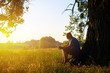 Aged man beneath a tree on the background of sunset in the field