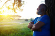 Side view of handsome aged man near the tree looking at the suns
