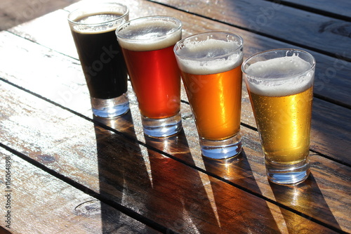 Juliste A selection of four craft beers during a tasting session on a wooden table