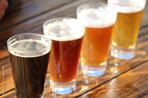 A selection of four craft beers during a tasting session on a wooden table Poster