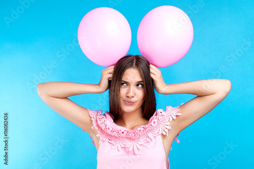 Funny young girl with pink balloons on head Poster