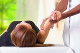 Woman lying down getting physical arm treatment from physio therapist, hands working on her elbow area, medical concept