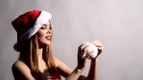 Blond girl in Santa's hat playing with xmas tree ball