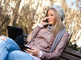 Young woman sitting in park, using laptop and talking on mobile phone