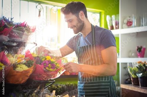Zdjęcia na płótnie, fototapety, obrazy : Male florist arranging bouquet of flower at flower shop