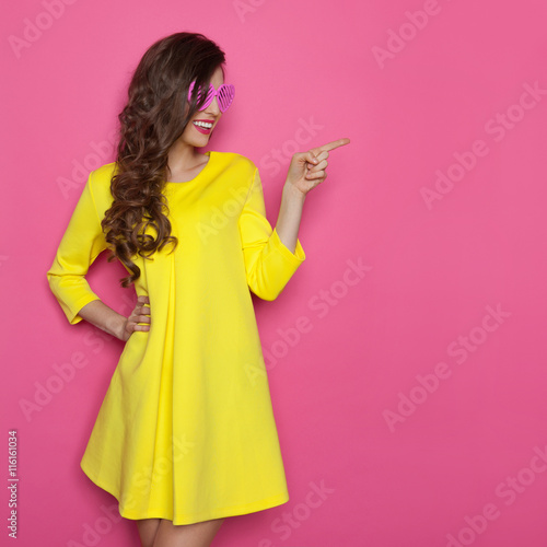 Girl In Yellow Dress And Pink Glasses Pointing - 116161034
