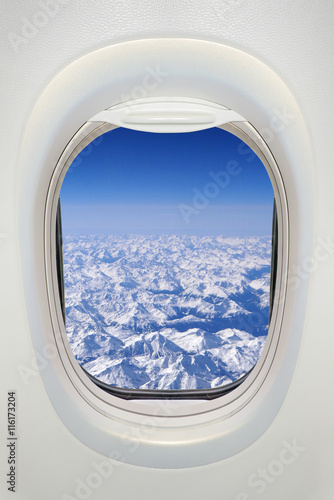 Window of an airplane from inside, view on snowy mountains (the Alps) - 116173204