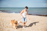 Smiling man jogging with his dog on the beach