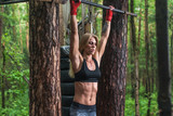 Fit woman preparing to do pull ups on horizontal bar.