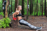 Fit woman doing triceps dips at park. Fitness girl exercising outdoors with own bodyweight
