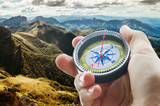 compass and hand in mountains