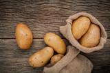 Fresh organic potatoes in hemp sake bags on rustic wooden backgr - 116204080
