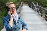 Mature woman with glasses waiting your call. Dressing in a denim jacket, a senior Caucasian lady is standing by river bridge holding a mobile phone and listening