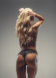 Topless blond female in black panties.