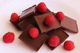 Dark chocolate stack with fresh raspberries on a light background