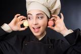 Chef donna su sfondo neutro scuro, dettaglio dolcetti.