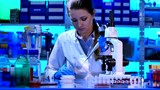 Female Scientist Looking Through Microscope in laboratory
