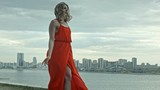 Attractive young woman in a red dress stands over the citi