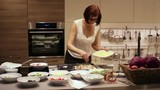 Woman Puts Cheese in Pizza Toppings