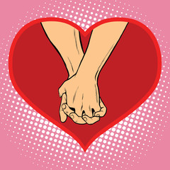 Male and female hand together in a red heart symbol of love
